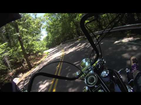 Harley- Davidson Softail Deluxe with apehangers leaning it way over in the twisties Video