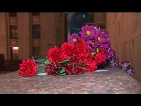 Люди несут цветы к зданию МИДа, чтобы почтить память Виталия Чуркина