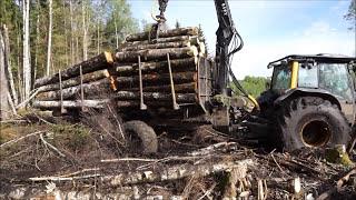 Valtra forestry tractor stuck in mud, trailer was broken