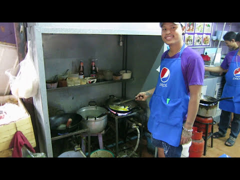 Cook prepares delicious food at street restaurant Sukhumvit road Bangkok