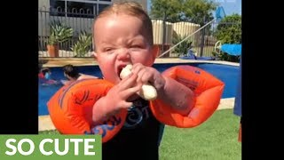 Baby attempts to eat banana while wearing floaties