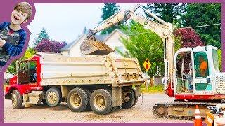 Excavator Loads Dump Truck At Construction Site