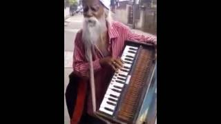 OLD man singing a song with a harmonium