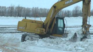 200 JD excavator cleaning snow out of ditches
