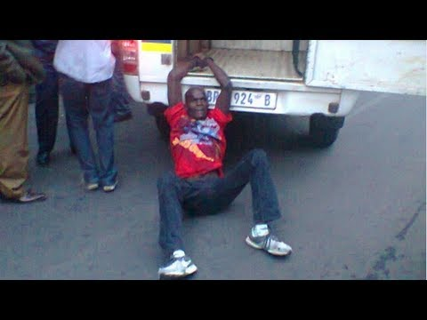 South African police drag handcuffed man behind van