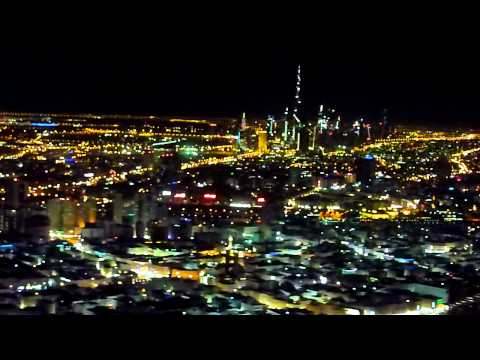 Night landing in Dubai with view of the Burj Khalifa and the Dubai Creek