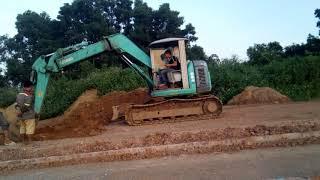 Máy Xúc mini mầu xanh đang xúc đất xây dựng-Bao Chau TV