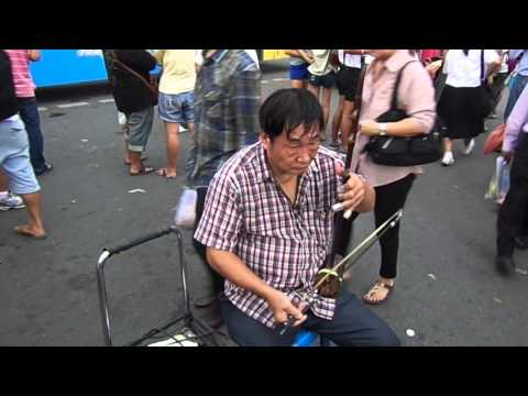 Elder man playing instrument in bangkok street (chatuchak weekend market) .MP4