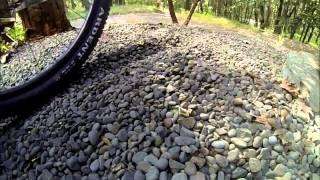 Wheels of different sizes roll across loose small rocks in slow motion.