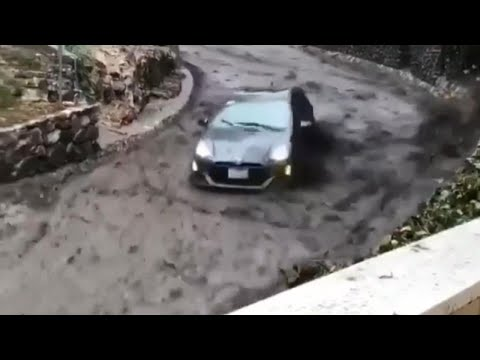 Car Speeds Down Road Trying To Escape Fast Moving River of Mud