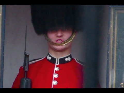 Queen's Royal Foot Guard at Buckingham Palace makes funny faces at a tourists in London.