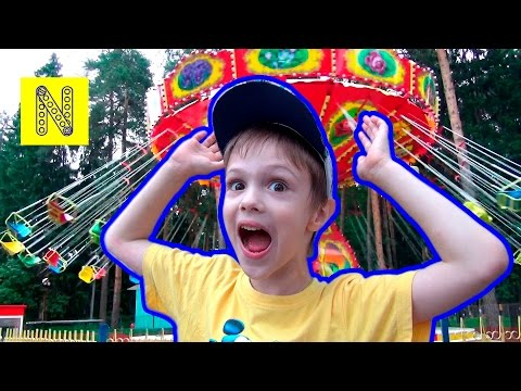 Дети в парке развлечений катаются на аттракционах. In the amusement Park