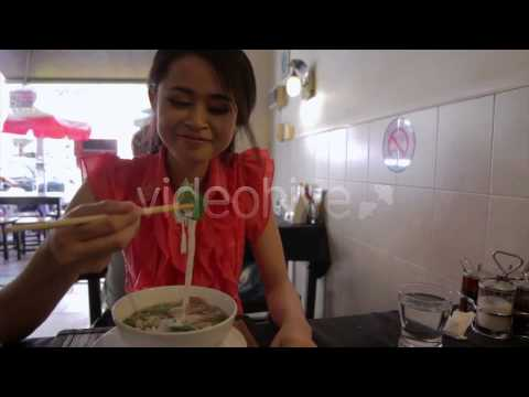 Stock Footage - Asian Girl Eating Noodles in a Local Restaurant | VideoHive
