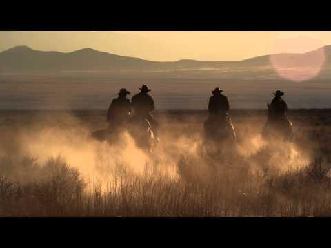 Slow motion dusk shot of cowboys riding towards mountains.