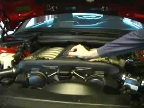 Монета стоит ребром на работающем двигателе BMW