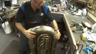 Brass instrument dent removal techniques. Tuba dents removed in bow