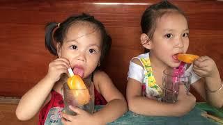 bé suti ăn kem cùng chị