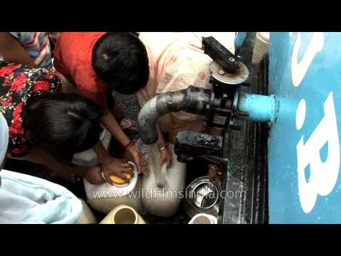 Delhi unauthorised colony dwellers collecting water from a government tanker
