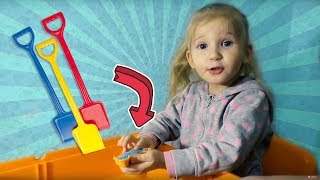 Play with sand molds and toy shovels on indoor colorful sandpit table