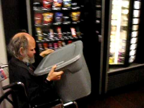 A blind man, in a wheelchair, at work filling a cold food vending machine.