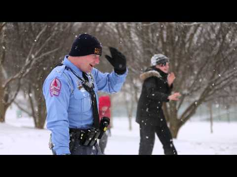 Raleigh police officers join in on a snowball fight and sledding at Lions Park