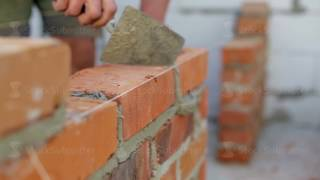 Workers hand lays bricks on a construction site