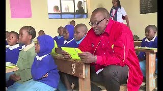 President Uhuru Reads with Small Children in Class.He sits on Wooden seats and Uses a Tablet.