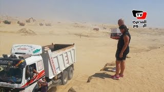 مواطن وابنته يوزعان مياه غازية على العاملين بقناة السويس الجديدة