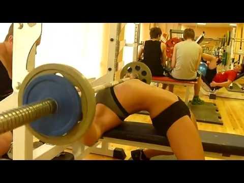 Сексуальная девушка жмет штангу в спортзале