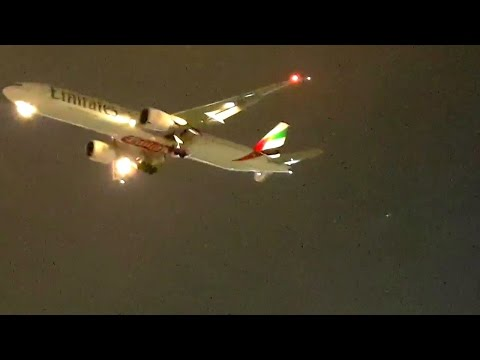 Flights landing at Dubai Airport in cloudy evening.
