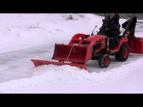 Snow blower, plow and bucket on Kubota BX clearing hard snow
