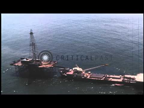 An offshore oil rig with a large barge secured to the rig in the Atlantic Ocean. HD Stock Footage