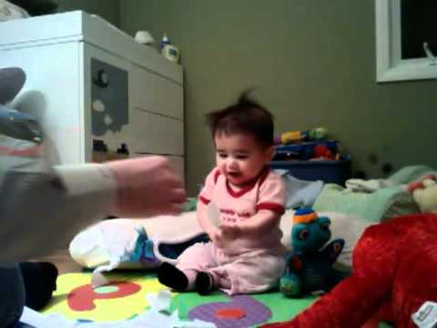 laughing baby tearing paper
