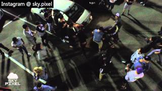 Drone captures fight in parking lot.