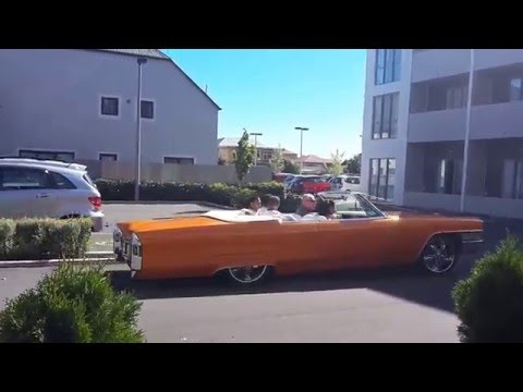 Groom arriving at his Indian wedding in an Orange Cadillac