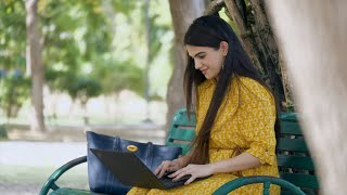 Indian woman happily using her laptop while sitting on a bench at the park - new technology