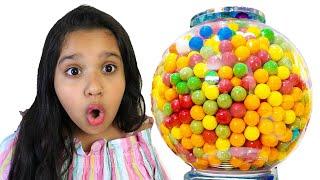 शफ़ा रंग बिरंगी ग़म बॉल मशीन के साथ खेलती है।