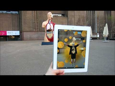 """All Hail Damien Hirst"" seen outside Tate Modern, London, with ""Hymn"" sculpture by Hirst"