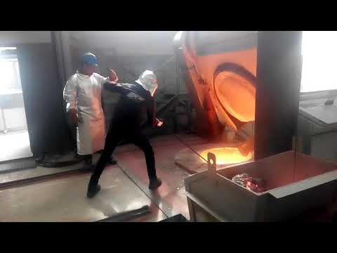 Removing slag from a molten metal furnace of 1400 C. (near view)