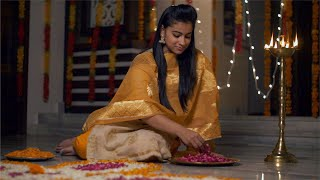 Diwali decoration - Gorgeous Indian girl / female making flower rangoli