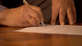 Senior man signing a legal document with a pen