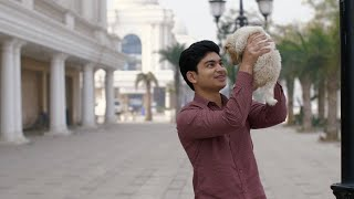 Handsome young guy having fun with his cute little puppy in the city market in India