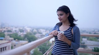 Indian girl drinking tea / coffee and looking at the view from balcony