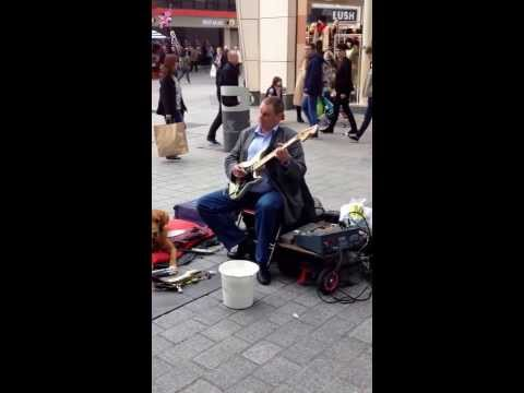 Blind man playing ghost rider on the guitar in liverpool town centre