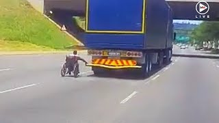 Wheelchair man catches a ride holding on to truck