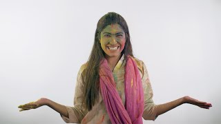 Happy young female throwing Gulal colors while celebrating Holi festival in India