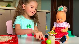 Маша играет с куклами с игрушечной посудой, делает песочные угощения
