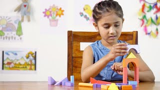 School going little girl playing with her wooden blocks to make a house - Learning