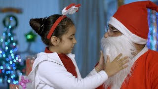 Smiling little girl in Santa hairband gives a tight hug to her loving Santa - Christmas time