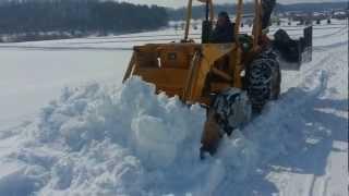 John Deere 300B Industrial tractormoving wet heavy snow.